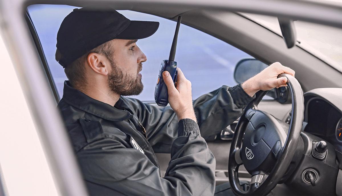 Agent de sécurité au volant de sa voiture, parlant dans un talkie-walkie